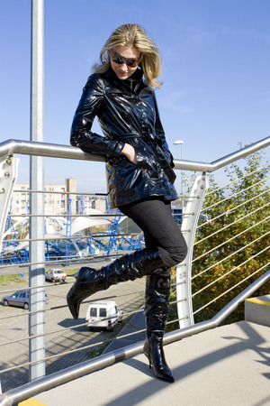 blond haired: standing woman wearing black clothes