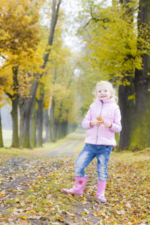 rubber boots: little girl wearing rubber boots in autumnal alley Stock Photo