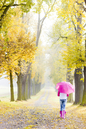 rubber boots: woman wearing rubber boots with umbrella in autumnal alley