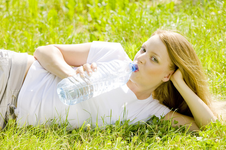 blond haired: lying woman with bottle of water Stock Photo