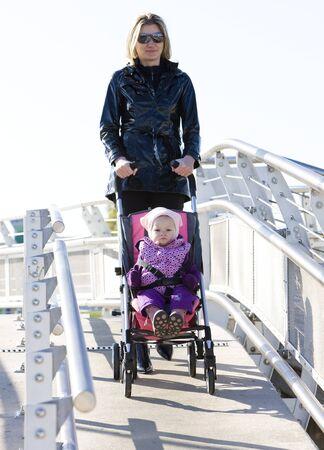 baby stroller: woman with toddler sitting in pram on walk