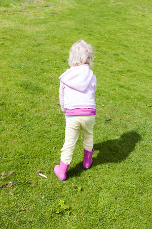 little girl wearing rubber boots on lawn