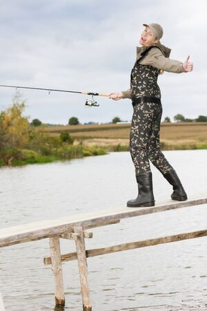 femme la pêche sur la jetée à l'étang