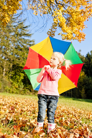 little girl with umbrella in autumnal nature