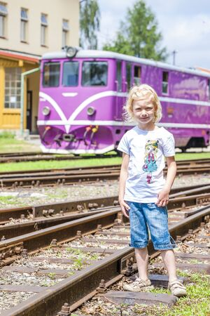 narrow gauge railroads: little girl at railway station of Nova Bystrice, Czech Republic Stock Photo