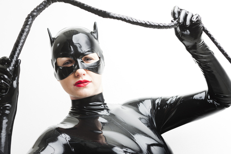 domina: portrait of standing woman wearing latex clothes with a whip