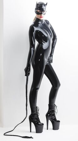 dominant: standing woman wearing latex clothes with a whip