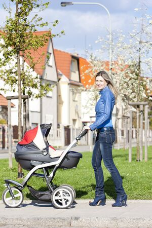 baby carriage: woman with a pram on spring walk Stock Photo
