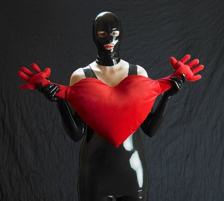 saint valentine   s day: woman in latex with heart