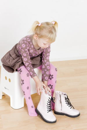 putting: little girl putting on boots