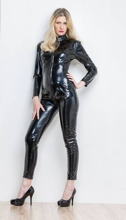 standing woman wearing black extravagant clothes and pumps