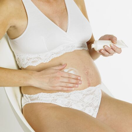 body lotion: pregnat woman putting on body lotion Stock Photo