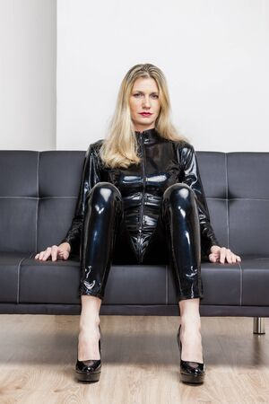 extravagant: woman wearing black extravagant clothes and pumps sitting on sofa