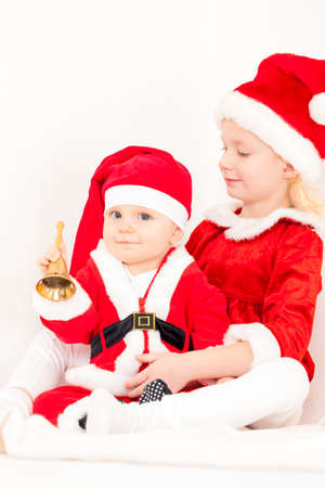 little bell: two little girls as Santa Clauses with a bell