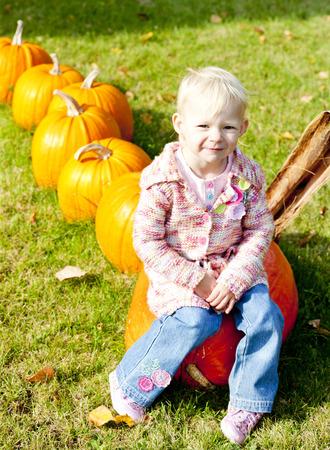 falltime: little girl with pumpkins Stock Photo