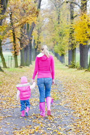 falltime: mother with her daughter in autumnal alley