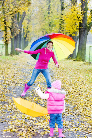 falltime: mother and her daughter with umbrellas in autumnal alley