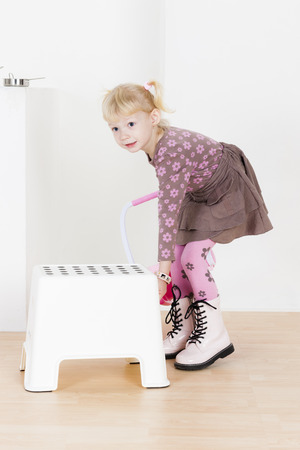 stool: standing little girl with a stool