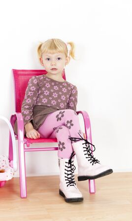 skirts: little girl sitting on chair Stock Photo