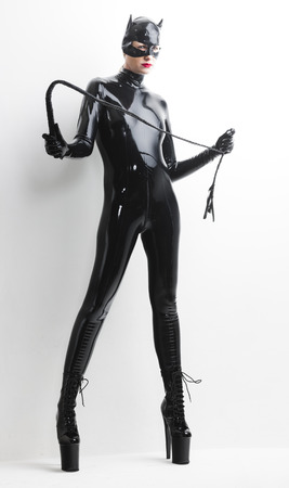 fetishism: standing woman wearing latex clothes with a whip