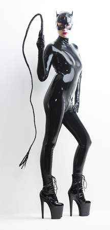 standing woman wearing latex clothes with a whip