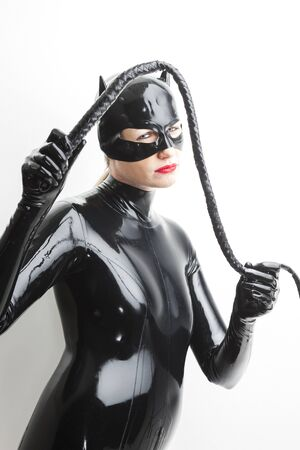 fetishism: portrait of standing woman wearing latex clothes with a whip