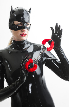 fetishism: portrait of woman wearing latex clothes with handcuffs