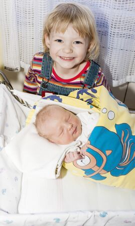 swaddling: portrait of a little girl with her newborn baby sister in maternal hospital