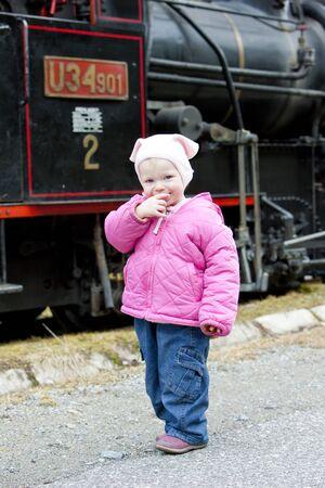 narrow gauge railroad: litte girl standing at steam locomotive, Ciernohronska Railway, Slovakia Stock Photo