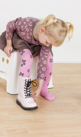 putting on: little girl putting on boots