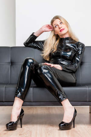 extravagance: woman wearing black extravagant clothes and pumps sitting on sofa