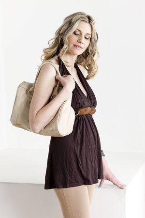 portrait of standing woman wearing summer clothes with a handbag photo