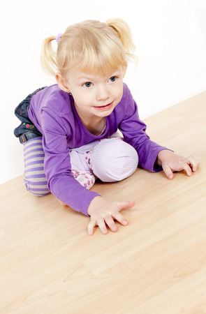 kneel down: little girl playing with a doll Stock Photo