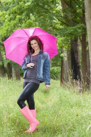 vrouw dragen van rubberen laarzen met paraplu in de lente natuur