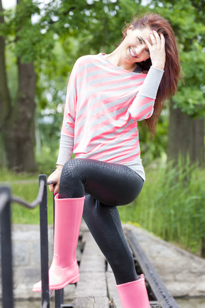 woman wearing rubber boots in spring nature
