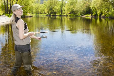 femme pêchant dans la rivière au printemps