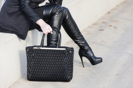 detail woman wearing boots with a handbag