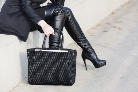 Detalle mujer con botas con un bolso de mano Foto de archivo