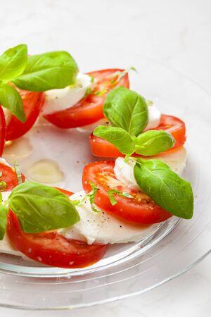 Délicieuse salade caprese avec tomates mûres et fromage mozzarella avec feuilles de basilic frais. nourriture italienne