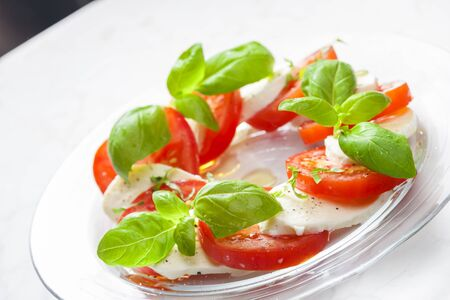Delicious caprese salad with ripe tomatoes and mozzarella cheese with fresh basil leaves. Italian food