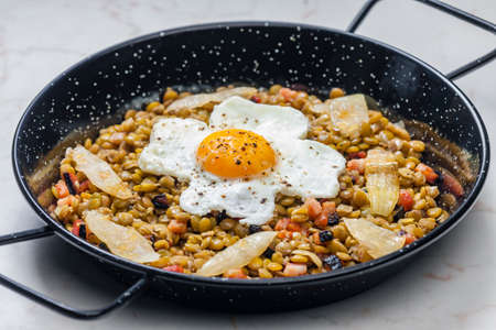 lentils with smoked meat and onion served with fried egg 写真素材