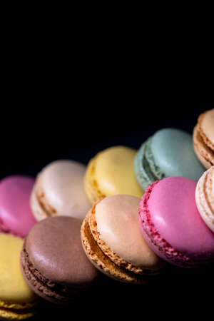 macaroons of different colors on a black background