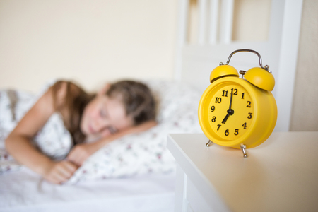 school child sleeps in bed. yellow alarm clock is on the table shows seven oclock.