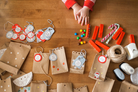 preparing the advent calendar. bags and sweets on the table. little baby arms to reach for the candy. Stock Photo