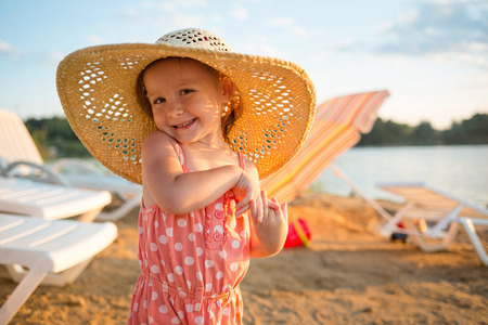 baby on the beach.girl Flirty in the hat on the background of sun loungers, sand and water. summer vacation with children.