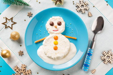 Fun food idea for kids. Christmas childrens Breakfast: snowman of cottage cheese on a blue plate