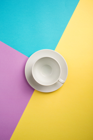 white empty coffee Cup on bright yellow-turquoise-purple background. copy spase, flat lay 스톡 콘텐츠
