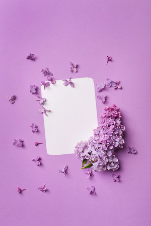 stylish postcard with fresh splendid lilac flowers and empty tag for your text on purple background.