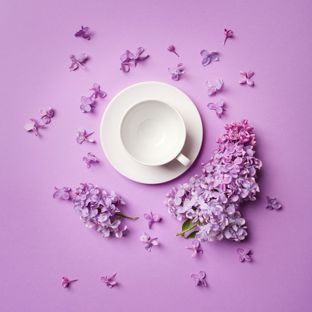 white empty coffee Cup on bright purple background with branches and lilac flowers. copy spase, flat lay.