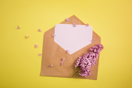 branch of purple lilac and the envelope with the letter on a yellow background. minimalism. 스톡 콘텐츠